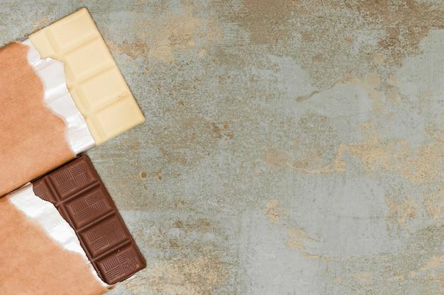 Leite e barra de chocolate escura no fundo grunge Foto gratuita
