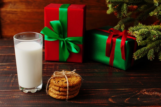 Leite e biscoitos para o papai noel debaixo da árvore de natal Foto Premium