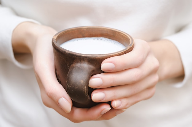 Leite fresco em um copo de barro nas mãos femininas Foto Premium