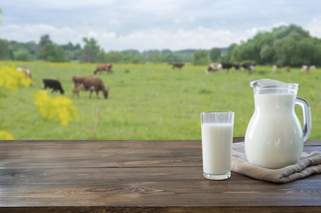 Leite fresco em vidro na mesa de madeira escura e paisagem borrada com vaca no prado. alimentação saudável. estilo rústico. Foto Premium