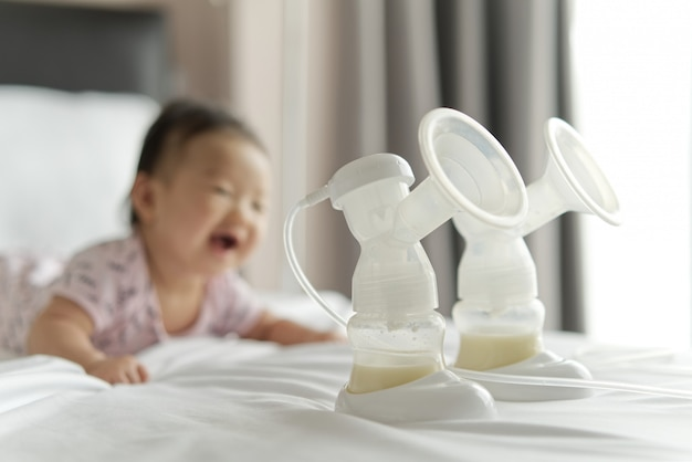 Leite materno nas garrafas da bomba de leite na cama com o bebê de sorriso que rasteja no fundo. Foto Premium
