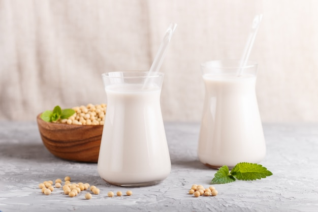Leite orgânico da soja de leiteria não na placa de vidro e de madeira com feijões de soja em um concreto cinzento. Foto Premium