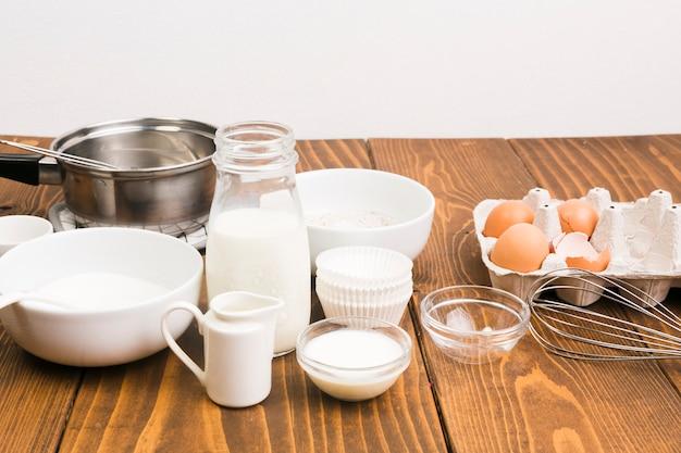 Leite; ovo; e utensílios de cozinha no balcão da cozinha Foto gratuita