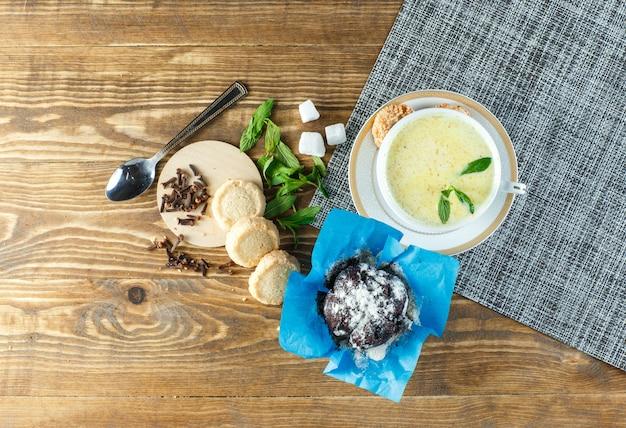 Leite picante com hortelã, colher, cubos de açúcar, biscoitos, cravo em um copo na mesa de madeira Foto gratuita