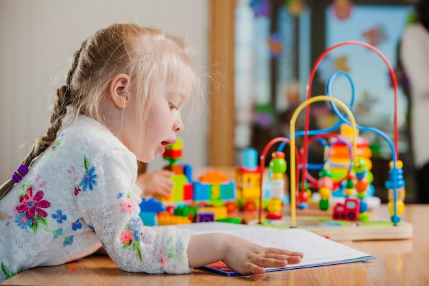 Leitura da menina no jardim de infância Foto gratuita
