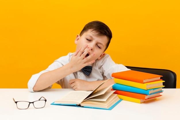 Leitura de menino sonolento de alto ângulo Foto gratuita