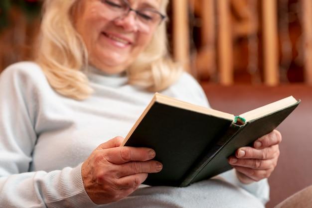 Leitura de mulher sorridente baixo ângulo Foto gratuita