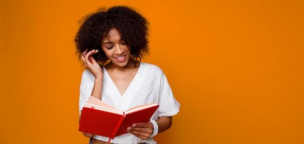 Leitura de sorriso feliz da mulher da raça da mistura com o livro do prazer sobre o fundo alaranjado. copie o espaço para texto. Foto gratuita