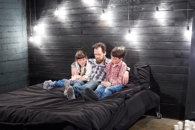 Leitura familiar da noite. pai lê as crianças um livro antes de ir para a cama Foto Premium