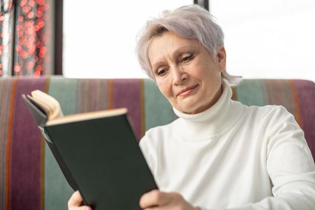Leitura feminina idosa de baixo ângulo Foto gratuita