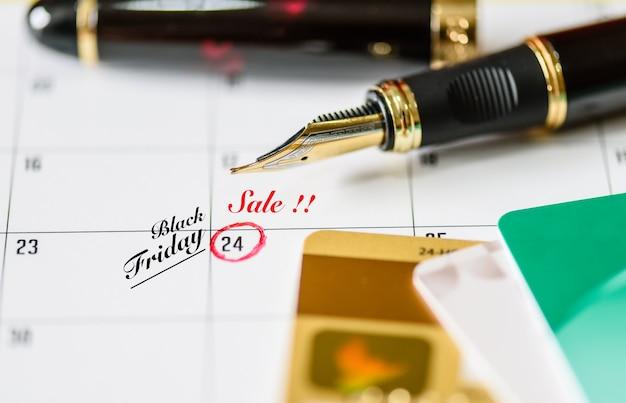Lembrete black friday sale no calendário branco com caneta preta e cartões de crédito Foto Premium