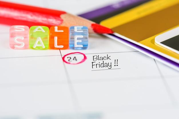 Lembrete black friday sale no calendário branco com caneta vermelha e cartões de crédito Foto Premium
