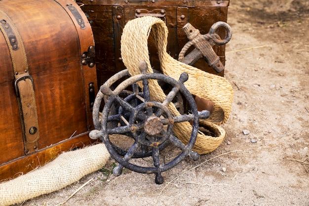 Leme de barco velho ao lado de uma âncora velha Foto Premium