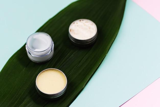 Lençol natural com cosméticos para o cuidado da pele e hidratação da pele do rosto e lábios. creme em uma jarra de plástico e em uma tigela de metal em uma folha de palmeira Foto Premium