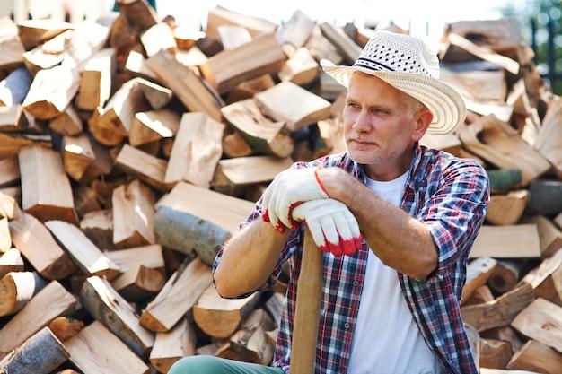 Lenhador maduro descansando após rachar madeira Foto gratuita