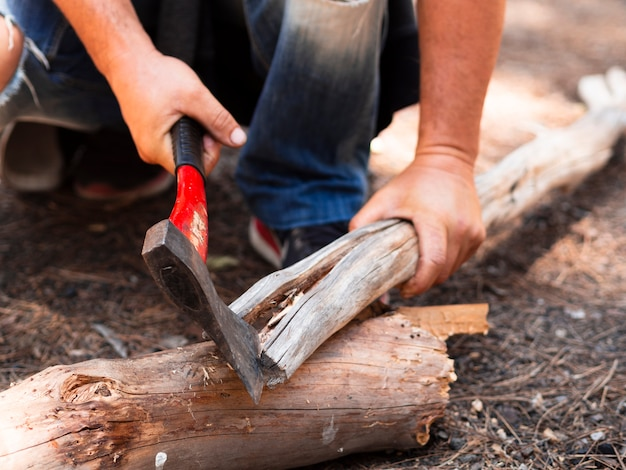 Lenhador sem rosto cortar log na floresta Foto gratuita