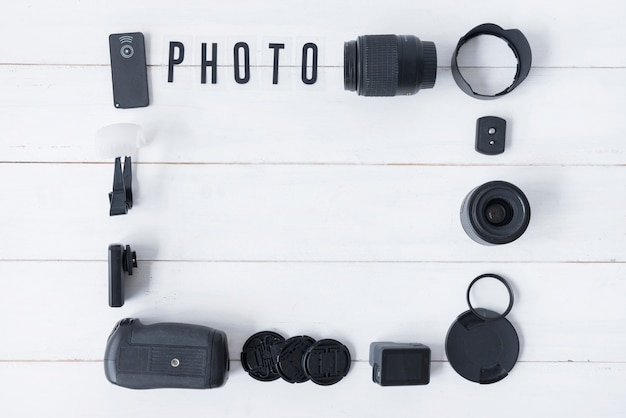 Lente de câmera com acessórios de fotografia e foto texto dispostas na mesa de madeira branca Foto gratuita