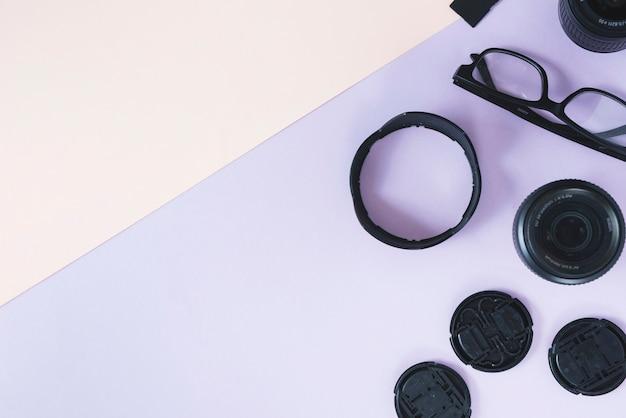 Lentes da câmera; anéis de extensão com acessórios de câmera e espetáculo em fundo duplo Foto gratuita