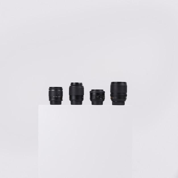 Lentes de câmera dispostas em bloco branco contra isolado no fundo branco Foto gratuita