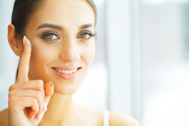 Lentes de contato de visão. closeup com rosto de mulher bonita Foto Premium