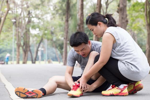 Lesão esportiva. homem, com, dor, em, hamstring, e, obtendo, ajuda, de, amigo Foto Premium