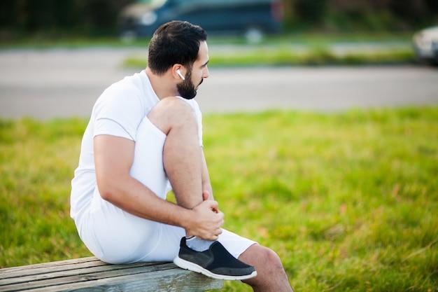Lesão na perna. atleta masculino que sofre de dor na perna durante o exercício ao ar livre Foto Premium