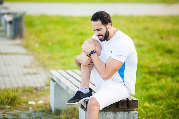Lesão na perna. atleta masculino, sofrendo de dor na perna durante o exercício ao ar livre Foto Premium