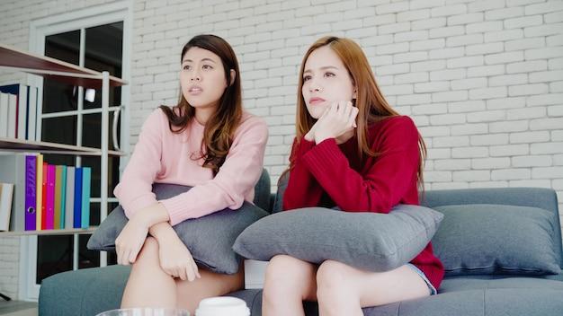 Lésbica asiática casal chorando enquanto assistia drama na tv na sala de estar em casa Foto gratuita