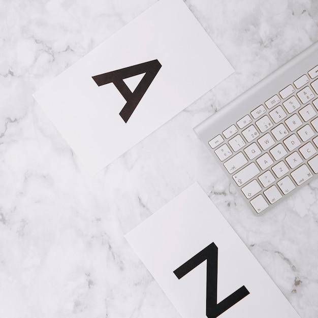 Letra a z em papel branco e teclado em mármore branco texturizado fundo Foto gratuita