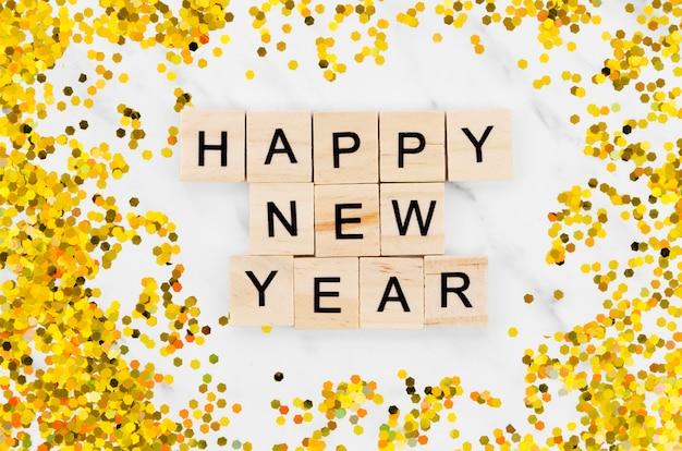 Letras de ano novo, cercadas por glitter dourado Foto gratuita