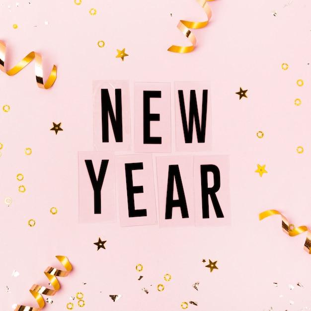 Letras de ano novo em fundo rosa com fitas douradas Foto gratuita