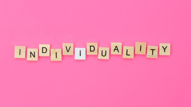 Letras de individualidade feitas com cubos de madeira no fundo rosa Foto gratuita