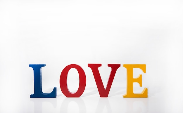 Letras de madeira coloridas amor sobre fundo branco. Foto Premium