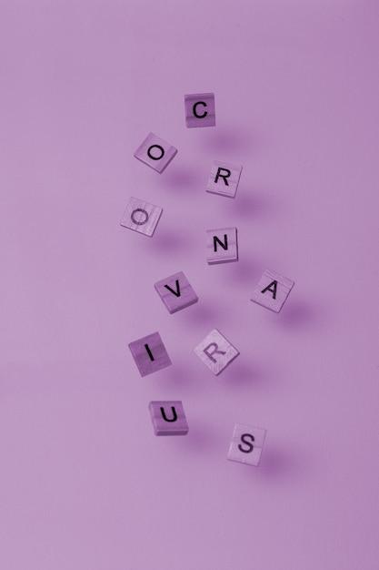 Letras de madeira espalhadas sob a forma da palavra roxo de coronavirus Foto Premium