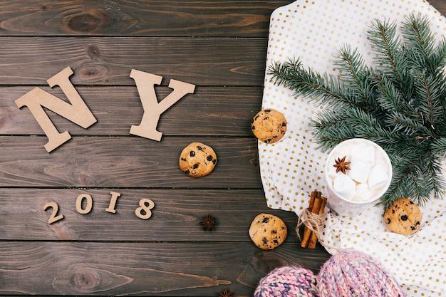 Letras de madeira 'ny 2018' encontram-se no chão cercado de biscoitos, ramos de abeto e meias quentes Foto gratuita