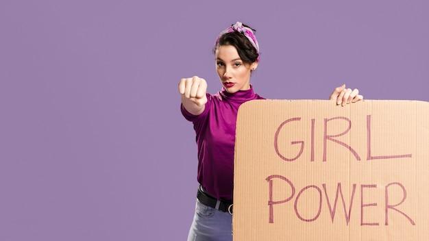 Letras de poder de menina em papelão e mulher mostrando o punho Foto gratuita
