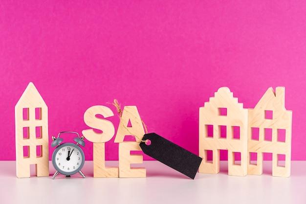 Letras de venda de madeira vista frontal ao lado de casas de madeira Foto gratuita