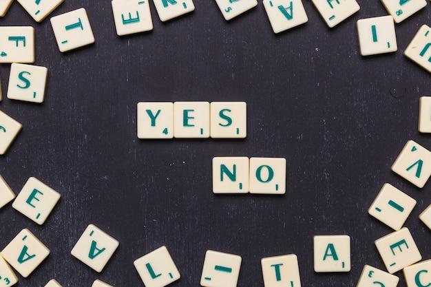 Letras sim ou não feitas de cartas de jogo scrabble contra fundo preto Foto gratuita