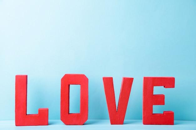 Letras vermelhas amor em azul. palavra de amor. Foto Premium