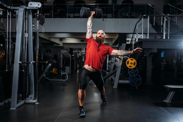 Levantador de peso forte com halteres, treino na academia Foto Premium