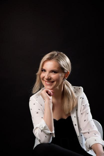 Levantamento novo da mulher de negócio isolado sobre o fundo preto da parede que senta-se em uma cadeira. Foto Premium