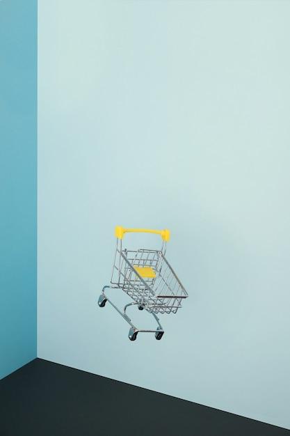 Levitando carrinho de compras em fundo azul Foto Premium