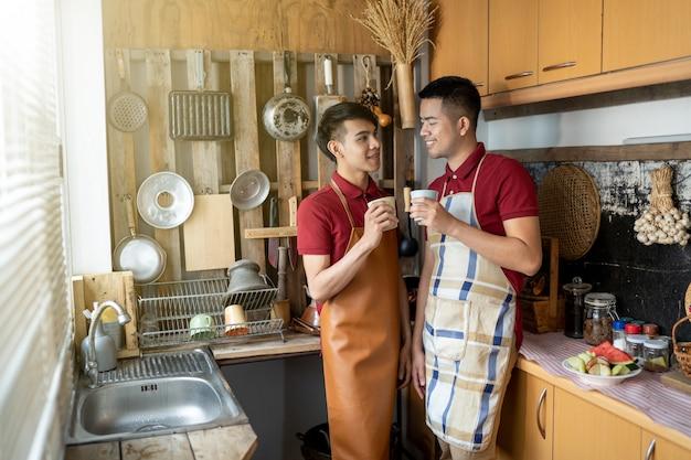 Lgbt homossexual masculino está ajudando a cozinhar alimentos na cozinha. Foto Premium