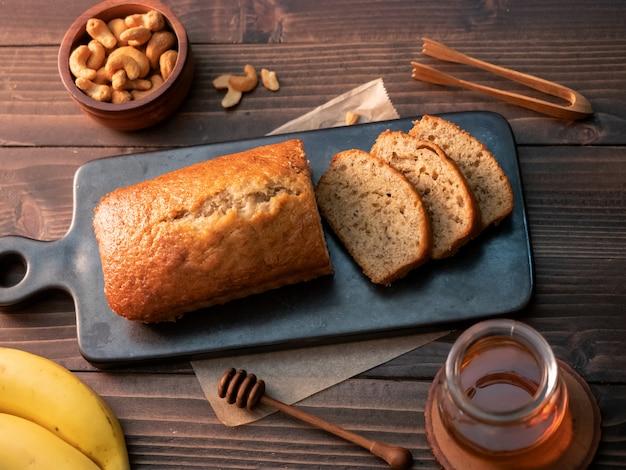 Libra caseiro do pão de banana cortada com porcas e mel de caju na tabela de madeira. Foto Premium