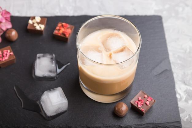 Licor de chocolate doce com gelo no copo e placa de ardósia de pedra preta. vista lateral Foto Premium