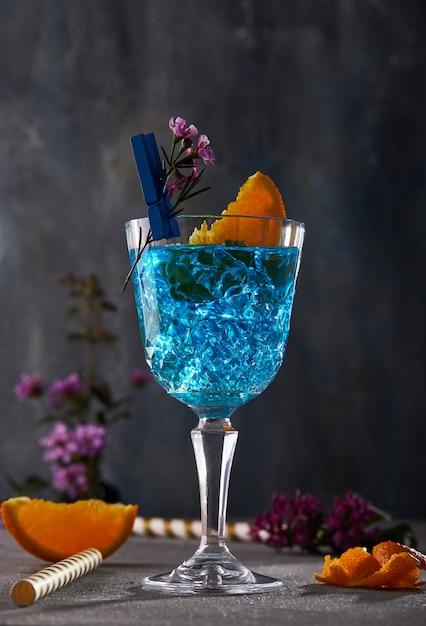 Licor de curaçao azul com laranja e flor para design Foto Premium
