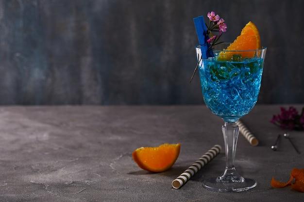 Licor de curaçao azul com laranja e flor para o projeto em uma mesa cinza Foto Premium