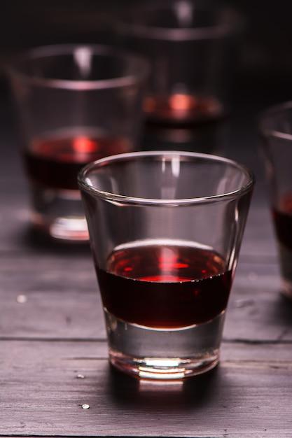 Licor de framboesa em tiros de vidro, foco seletivo Foto Premium