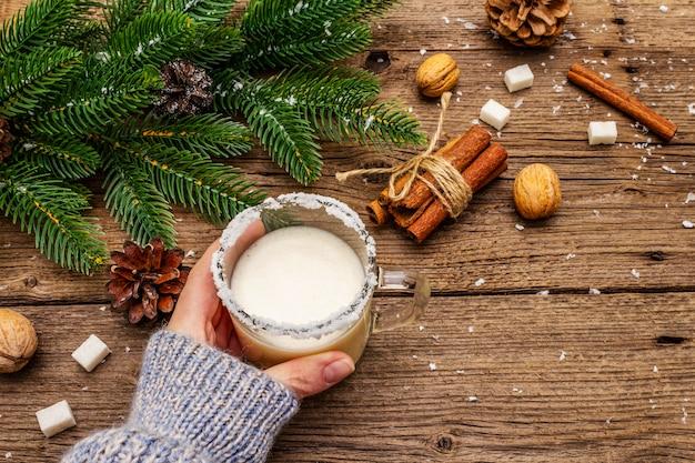 Licor de gemada de natal ou coquetel de cola mono. bebida clássica de inverno na caneca de vidro, decorações de natal. mão de mulher em jersey. Foto Premium