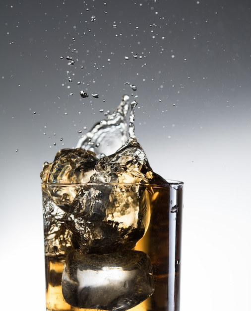 Licor de uísque cocktail respingo álcool em vidro Foto Premium